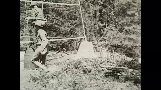 1930s: Text on screen. Men rise from logs and approach steel lookout tower. Men remove jackets and climb up ladder.