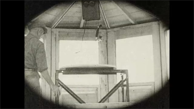1930s: Men climb up ladder with support cage. Men enter wooden cabin atop lookout tower.
