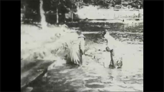1930s: UNITED STATES: men catch salmon. Men lift salmon onto bank. Man hits salmon on head.