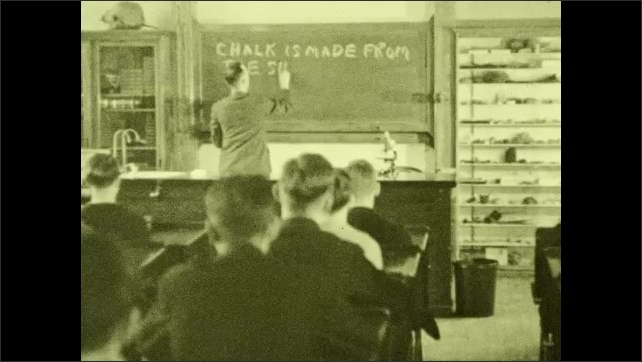 1930s: UNITED STATES: teacher writes on board with chalk. Chalk is made from the shells of tiny sea animals. Man puts chalk on desk