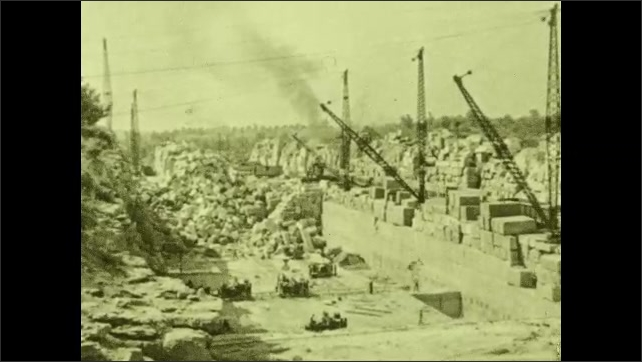 1930s: UNITED STATES: view across large building site. Train approaches warehouse