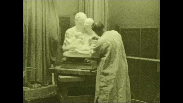 1930s: UNITED STATES: man carves stone block. Man uses knife and paper