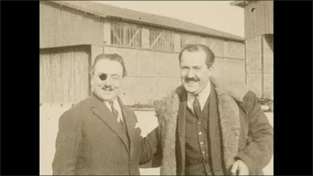 """1920s:Man in uniform studded with medals nods at camera. Two mustachioed men, one with an eyepatch, pose together. Intertitle """"The fateful start from Paris""""."""