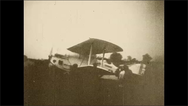 1920s:??Lindbergh climbs into cockpit and men help move the plane. Bi-plane takes off from field.