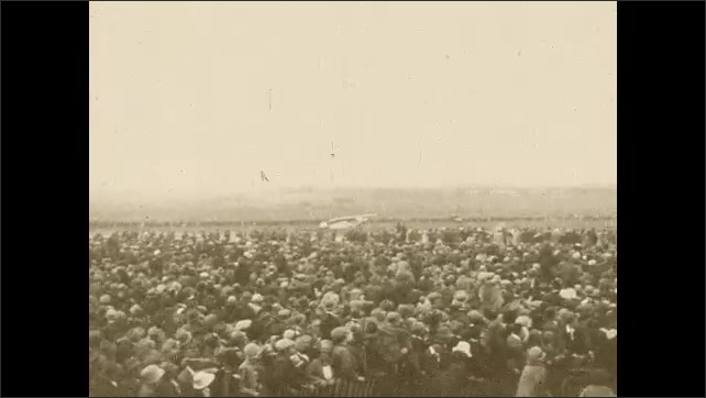 1920s:Huge crowd gathered to watch the Spirit of St. Louis land. Multiple planes also landing and taking off at the same time. People in crowd jump over each other to get closer.