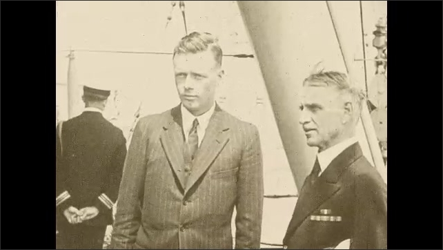 1920s:??A large crowd cheers and waves for Lindbergh. Lindbergh stands next to uniformed Officer and looks at the crowd. Pilot and co-pilot in the plane.??