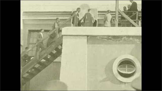1920s:Men in hats walk and climb stairs to a large dais.