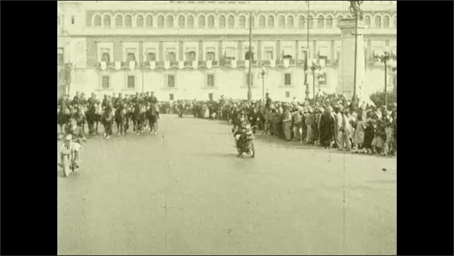 1920s:??Men in uniform ride motorcycles and cars through a parade route. Crowds watch Lindbergh wave from an open car.??