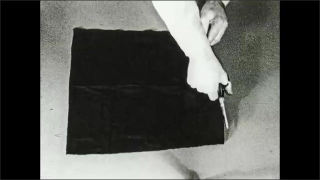 1930s: Hands measure cloth on tabletop. Hands fold cloth and cut with scissors. Hands fold cut cloth and sew edge with thread and needle.