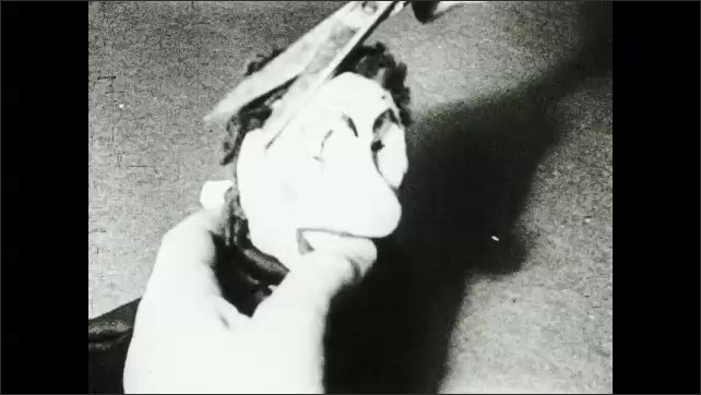 1930s: Hands apply glue from bottle to puppet head. Hands use stick to apply yarn hair to puppet head. Hands use scissors to trim yarn hair. Man cuts and applies pieces of yarn to puppet head.