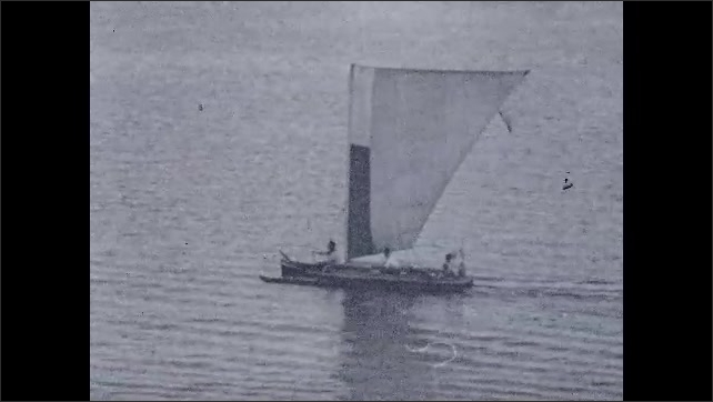 1930s: Boat travels across water. Small boats sail around bay.