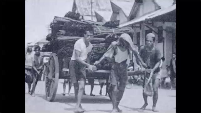 1930s: Man pulls cart full of sacks down street. Men pull and push cart full of plant bundles through street.