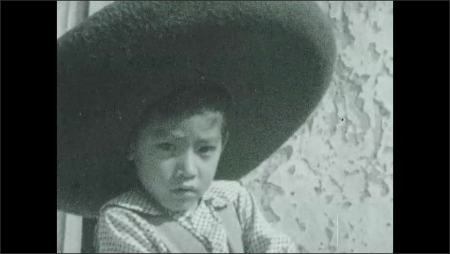 1930s: Boy combing hair. Close up, boy in sombrero. Boy feeding chickens. Baby chicks eating.