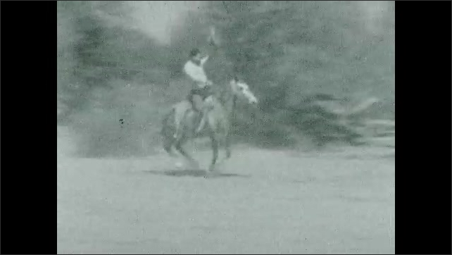 1930s: Man riding horse by man with lasso.