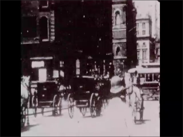 1950s: Streetcar, cars, horses and carriages, and pedestrians navigate busy street in film from early 20th century.