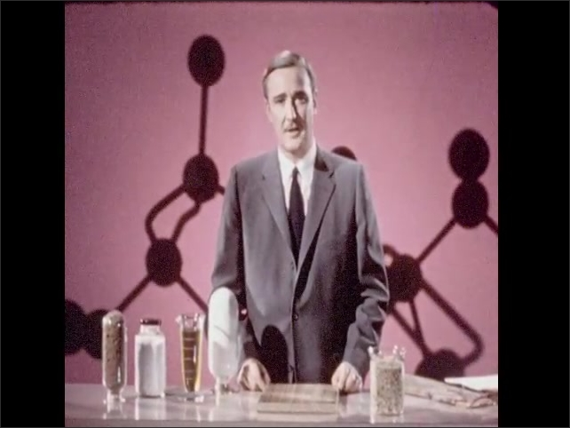 1950s: Man gestures to beaker holding oil. Man gestures to jars holding white substance and brown material.