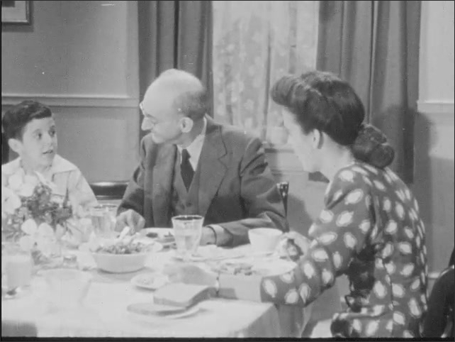 1940s: A family sits around a dinner table, talking, eating, and laughing. The father rises from his chair.