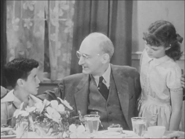 1940s: A man sits at a dinner table with his arms around a boy and a girl. They smile and talk.
