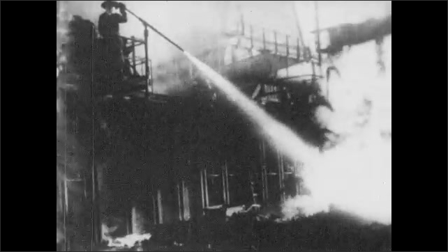 1930s: Construction site.  Men try to put out fire.