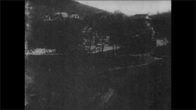 1930s: City.  Trees.  Children swing on playground.