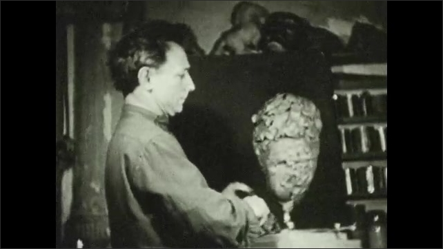 1930s: UNITED STATES: man carves out eyes on clay model. Man pats down clay