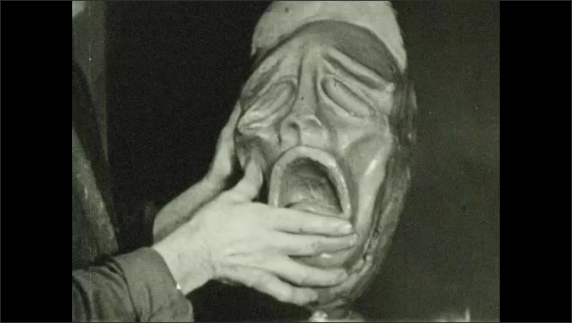 1930s: UNITED STATES: artist creates facial features in clay. Model of head and face