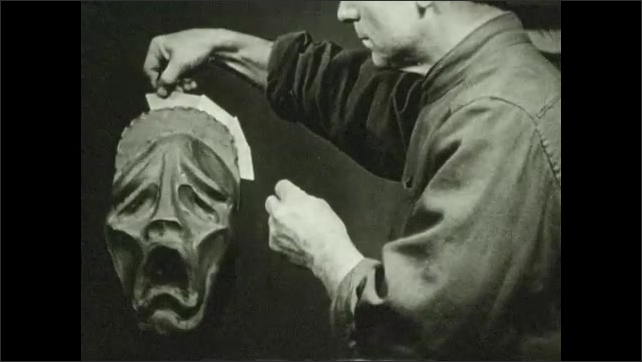 1930s: UNITED STATES: artist inserts slides into clay. Back of clay model of head