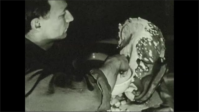 1930s: UNITED STATES: artist creates plaster head. Artist destroys bubbles in plaster by blowing. Man covers clay head with plaster