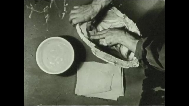 1930s: UNITED STATES: man covers paper strips with paste. Man sticks paper into mould