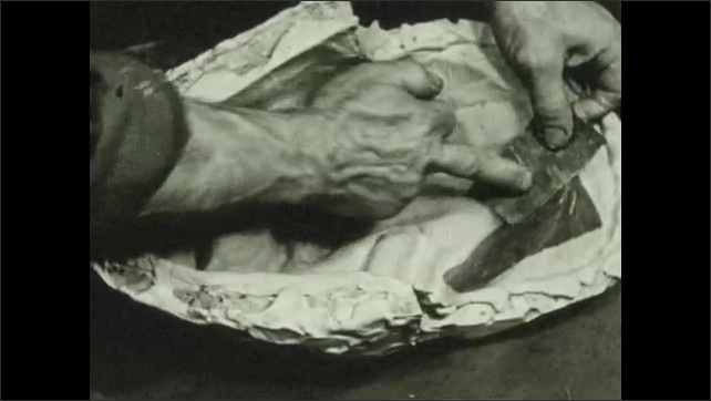 1930s: UNITED STATES: hands cover mould with paper and paste.