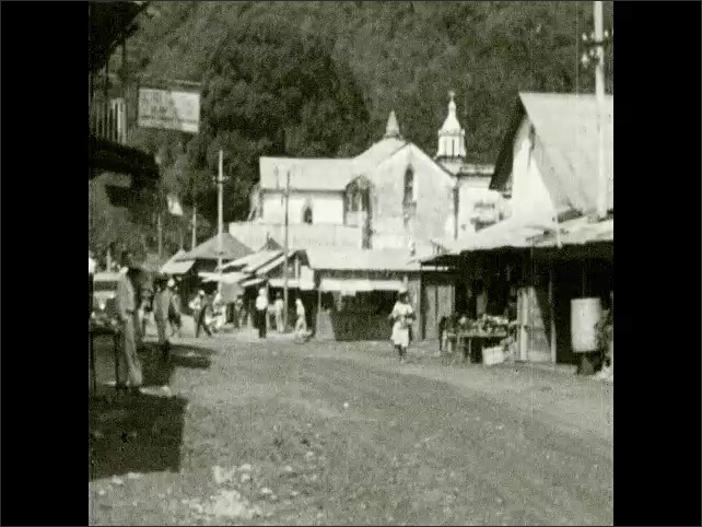 1930s: Men and women walk down dirt road in small town, People walk through small mountain town.