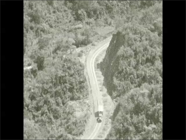 1930s: Truck drives up winding dirt road in mountains. Road winds from mountain valley through hills.