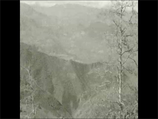 1930s: Car drives up winding mountain road. Clouds and mist hang over mountain valley in Mexico.
