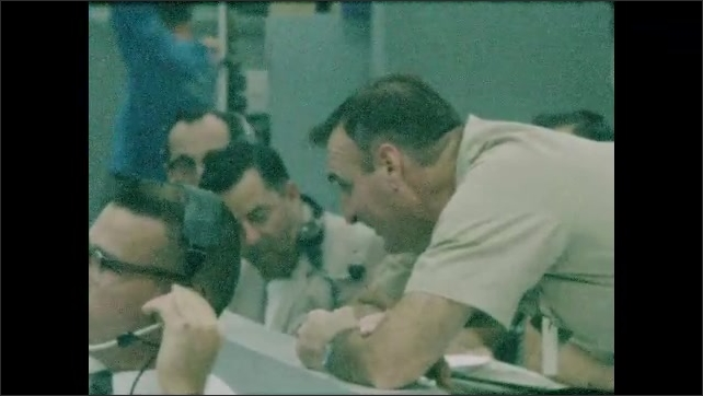 1960s: Control room.  Men sit.  Man leans on counter and talks.  Man talks on telephone.