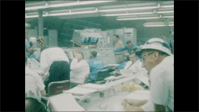 1960s: Control room.  Men work.  Man walks past and leans on counter.