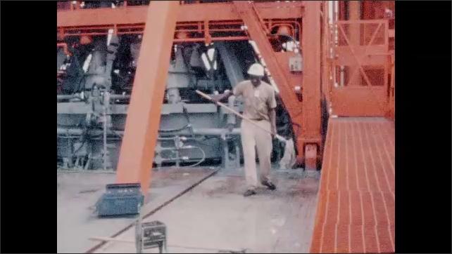 1960s: Launch pad.  Men mop floor.  Man wrings water from mop.