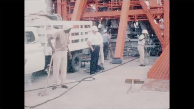 1960s: Launch pad.  Men mop.  Men stand near truck.  Men wait and talk.
