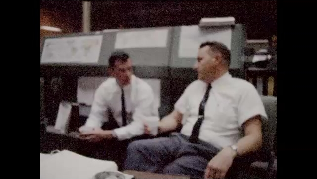 1960s: Control room.  Men sit at computers and work.  Men drink coffee and talk.