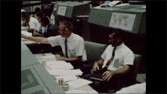 1960s: Control room. Men sit at computers and work.