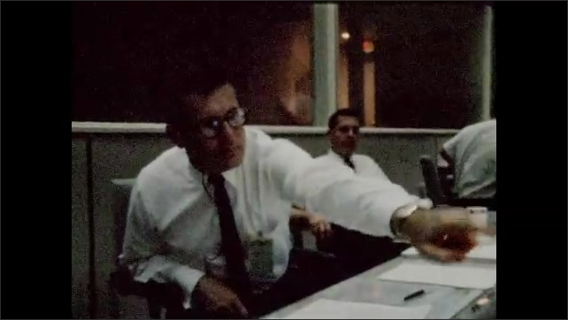1960s: Control room.  Men sit and work.  Man pushes button.  Man yawns.
