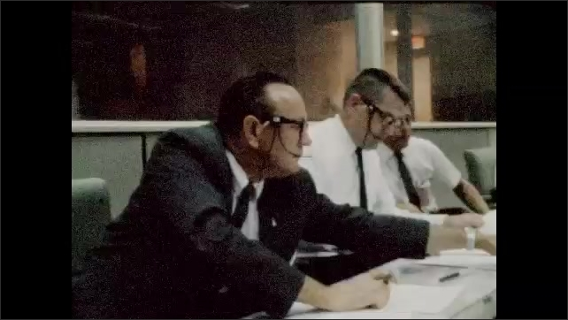 1960s: Control room.  Men sit and work.  Men look at papers together.