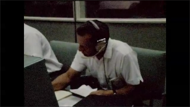 1960s: UNITED STATES: Film roll artifacts. Man speaks on headset. Man takes notes