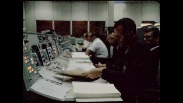 1960s: UNITED STATES: men work at NASA command center. Man looks through papers