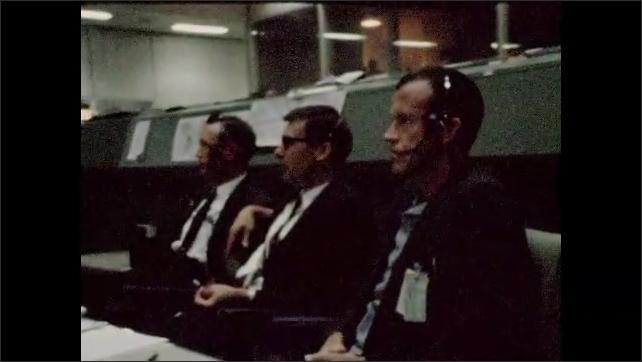 1960s: UNITED STATES: men sit at long desks at mission control. Men listen to headsets.