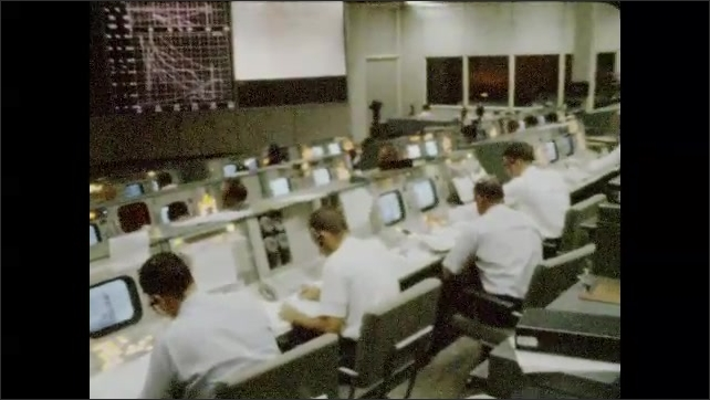 1960s: UNITED STATES: men sit at computers during spaceship launch. Men in white shirts sit at screens. Man speaks into headset