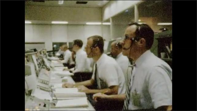 1960s: UNITED STATES: side profile of men during mission control tasks