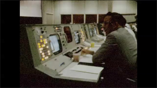 1960s: UNITED STATES: NASA employee works at control panel during launch. Workers in room during launch