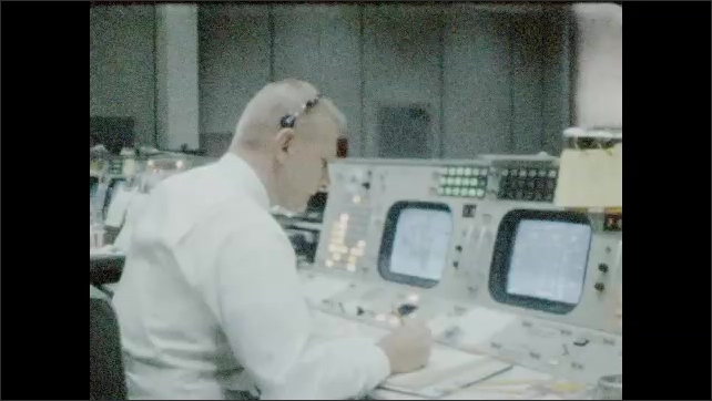 1960s: UNITED STATES: men gesture with arms during space flights. Man writes notes. View of large screen in NASA control center