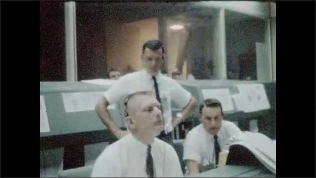 1960s: UNITED STATES: man pulls face during thoughts. Man speaks through headset microphone. Men follow progress of rocket launch. Computer screens at NASA mission control center