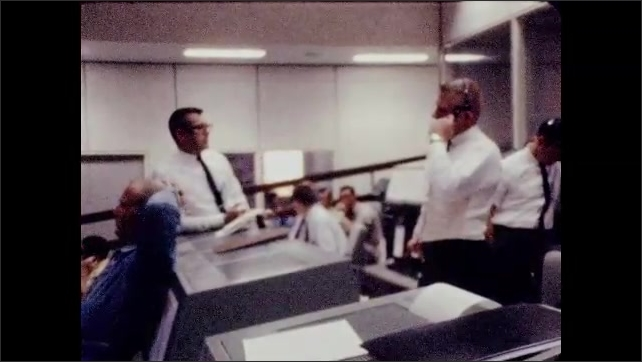 1960s: Men talking at control panel, man points to screen. Men standing by monitors, pan to men at control panel.